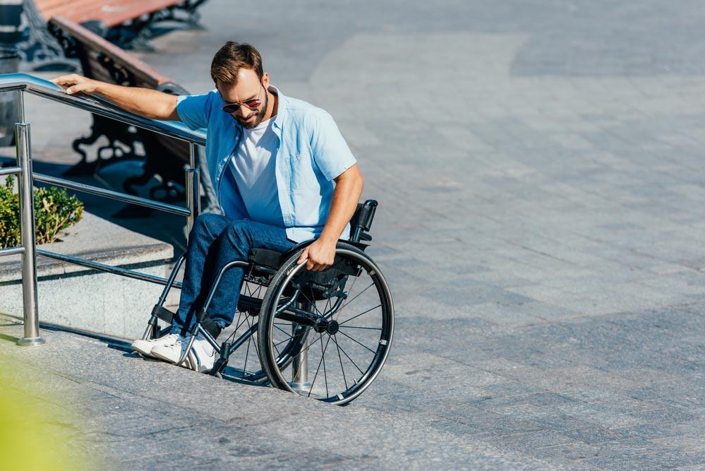 Minusválido en silla de ruedas con problemas para subir bordillo